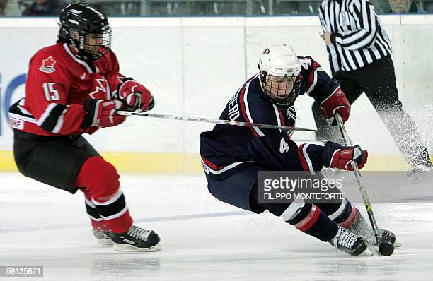 US Angela Ruggiero is tackled by Danielle Goyette of Canada during the Torino Ice 2005 Ice Hockey Tournament preliminary group A game at the renewed...