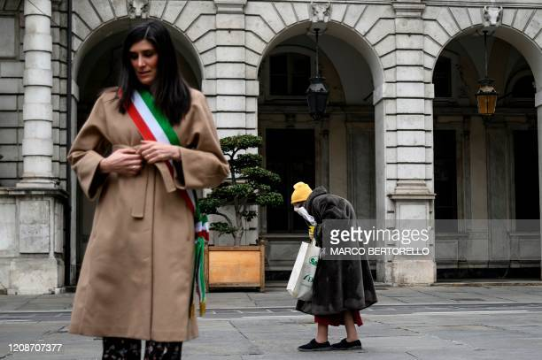 Turin mayor Chiara Appendino stands at attention as an elderly woman walks past during a minute of silence at noon on March 31, 2020 in Turin as...