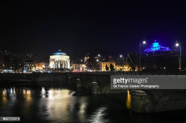 "turin skyline illuminated at night with ""vittorio emmanuele ii"" bridge, ""gran madre"" di dio church and ""monte dei cappuccini"" church on top of the hill in piedmont, italy - fiume po foto e immagini stock"