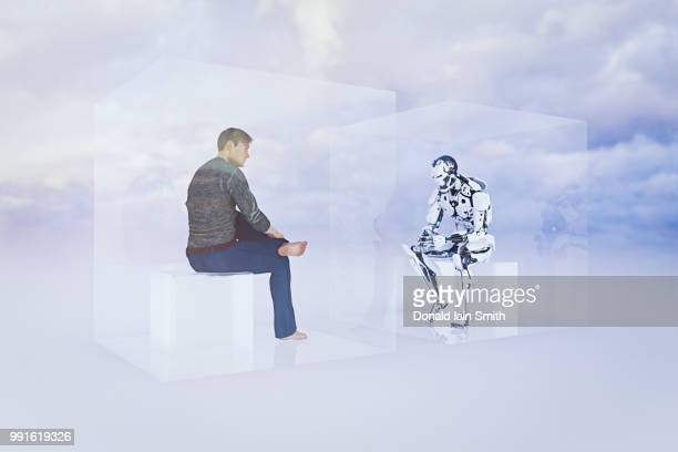 Turing test: robot versus human sitting inside cubes facing each other