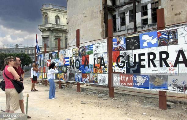 Turistas observan un cartel contra la guerra en Irak realizado por diferentes pintores cubanos en una calle de La Habana Vieja el 30 de marzo de 2003...
