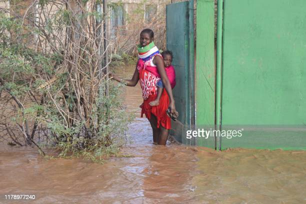 Turkana woman stops at a gate of her house that is submerged by flooded water after heavy rain in Lodwar, northwestern Kenya on October 18, 2019.