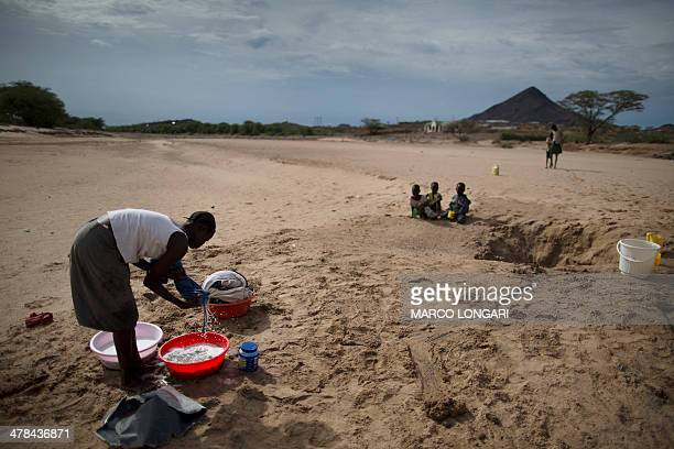 A Turkana woman washes clothes using water she scooped from a dry river bed in Lodwar on March 13 2014 A first downpour relieved pastoralists in the...