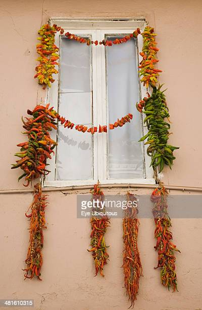 Turkey Aydin Province Kusadasi Strings of red green and orange chili peppers strung up to dry in summer sunshine from the window frame of house in...