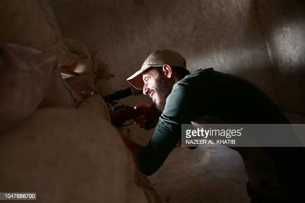 Turkey backed Syrian rebelfighter aims his rifle near the city of alBab in the Aleppo province on the border with Turkey on October 8 2018 Jihadist...