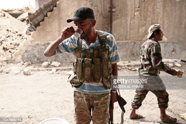 A Turkey backed Syrian rebelfighter drinks a coffee near the city of alBab in the Aleppo province on the border with Turkey on October 8 2018...
