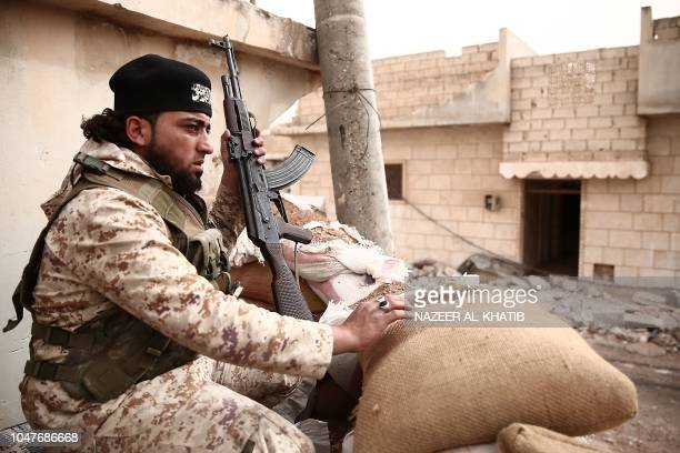 A Turkey backed Syrian rebelfighter holds his rifle near the city of alBab in the Aleppo province on the border with Turkey on October 8 2018...