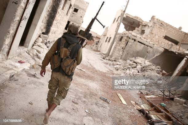 Turkey backed Syrian rebelfighter patrols with his rifle near the city of alBab in the Aleppo province on the border with Turkey on October 8 2018...