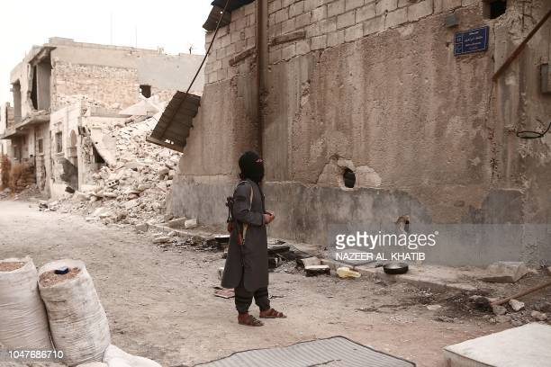Turkey backed Syrian rebelfighter reads a street plaque near the city of alBab in the Aleppo province on the border with Turkey on October 8 2018...