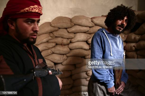 Turkey backed Syrian rebel-fighters hold their rifle near the city of al-Bab, in the Aleppo province on the border with Turkey, on October 8, 2018. -...