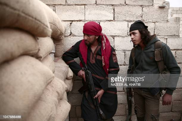 Turkey backed Syrian rebelfighters look trhough sand bags near the city of alBab in the Aleppo province on the border with Turkey on October 8 2018...