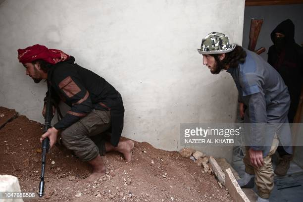 Turkey backed Syrian rebelfighters monitor a building near the city of alBab in the Aleppo province on the border with Turkey on October 8 2018...
