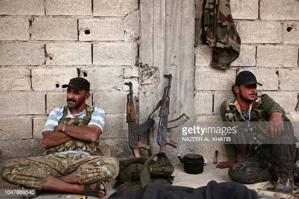 Turkey backed Syrian rebelfighters wait next to their rifles near the city of alBab in the Aleppo province on the border with Turkey on October 8...