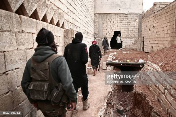 Turkey backed Syrian rebelfighters walk by a trench near the city of alBab in the Aleppo province on the border with Turkey on October 8 2018...
