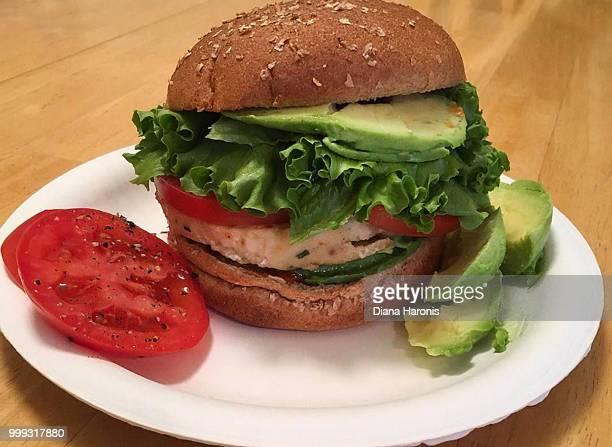 A turkey burger with avocado on a bun