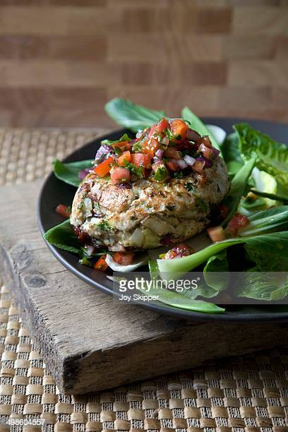 Turkey burger with salsa and salad on brown plate