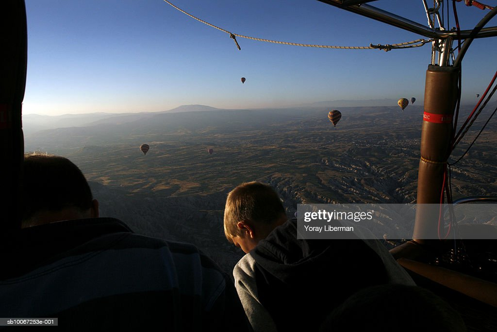 Turkey, Cappadocia, boy (12-13) in hot air balloons over countryside : Nachrichtenfoto