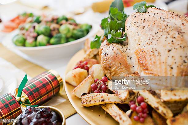 Turkey, cranberries and Christmas cracker on table