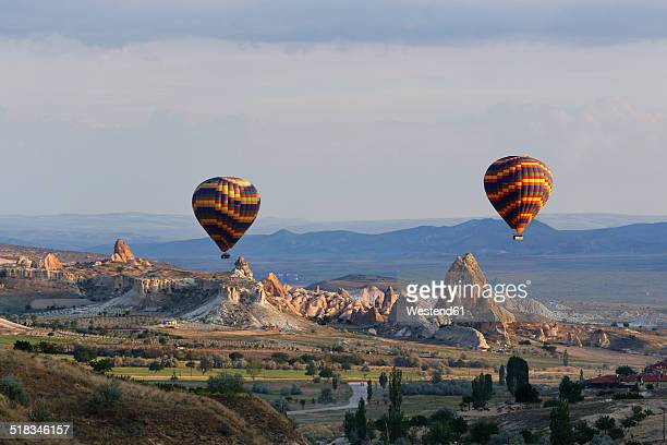 Turkey, Eastern Anatolia, Cappadocia, two hot air balloons hoovering over tuff rock formations at Goereme National Park