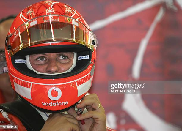 Ferrari German driver Michael Schumacher adjusts his helmet in the pits of the Istanbul racetrack during the second free practice session two days...