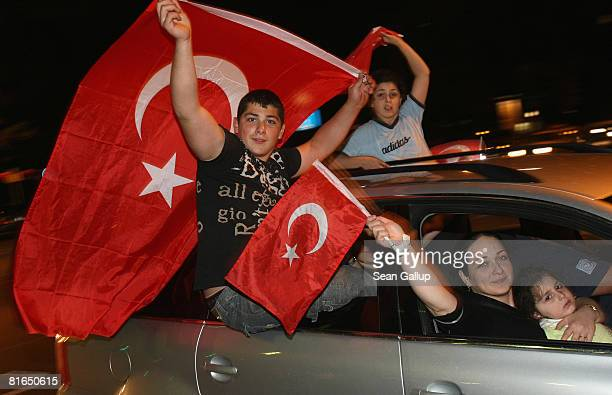 Turkey football fans wave Turkish flags as they hang out of their cars as they celebrate Turkey's victory over Croatia in the Euro 2008 quarter...