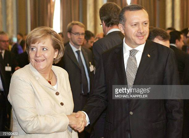 German Chancellor Angela Merkel and Turkish Prime Minister Recep Tayyip Erdogan shake hands before attending a meeting with Turkish and German...