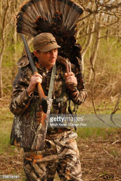 turkey hunter carrying dead turkey - turkey hunting stock photos and pictures