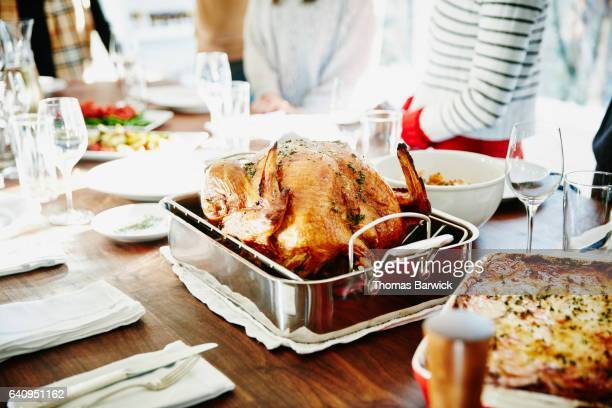 turkey in roasting pan on table for holiday meal - thanksgiving holiday stock pictures, royalty-free photos & images