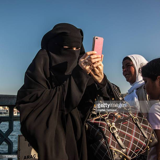 CONTENT] Turkey Istambul Galata bridge Woman in black tchador take picture with a pink smartphone