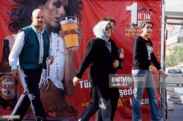 Turkey, Istanbul: a turkish model on the poster advertises for a foreign beer in front of the Carrefour
