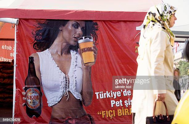 a turkish model on the poster advertises for a foreign beer in front of the Carrefour