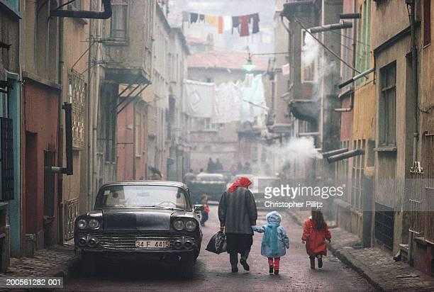 Turkey, Istanbul, Grandmother walking with grandchildren in street