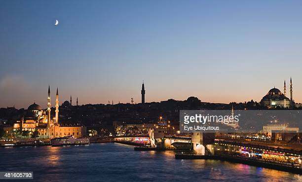 Turkey Istanbul Sultanahmet The Golden Horn The New Mosque or Yeni Camii at left the Galata Bridge and Suleymaniye Mosque at right illuminated at...