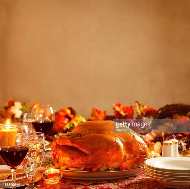 Turkey on platter in a Thanksgiving dinner setting