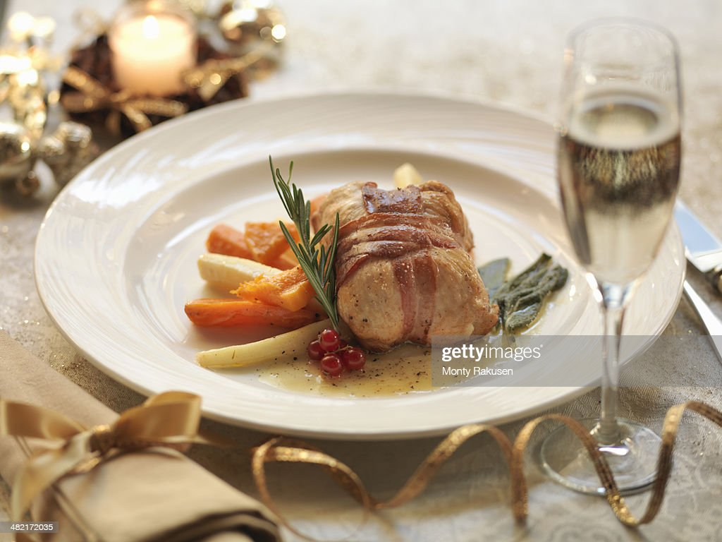 Turkey parcel wrapped in pancetta, stuffed with cranberry and orange and served with lemon and sage sauce with roasted winter vegetables, amid festive decorations : Stock Photo