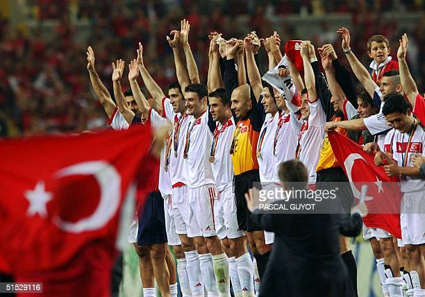 Turkey players salute the fans with medals around their necks 29 June 2002 at the Daegu World Cup Stadium in Daegu following the thirdplace playoff...