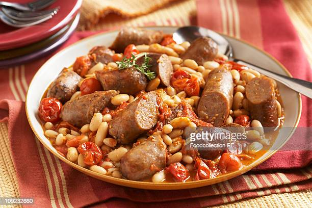Turkey sausage stew with cannoli beans and tomatoes in bowl, close-up