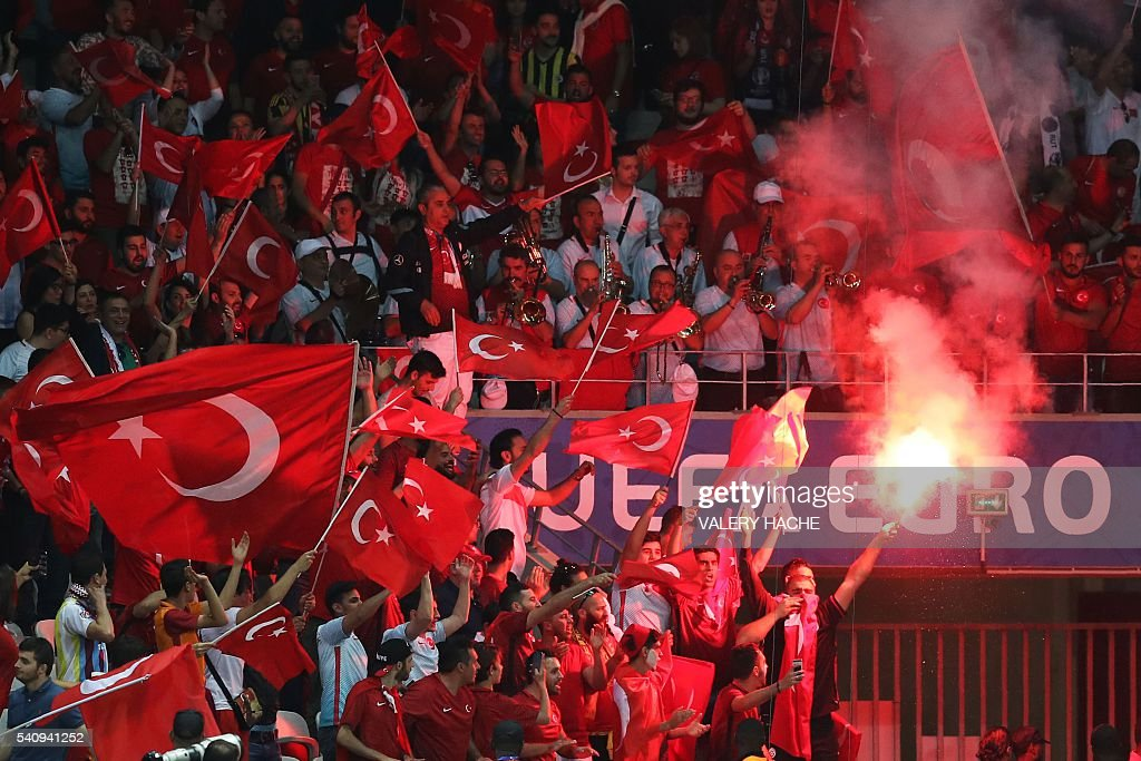 Turkey supporters wave the national flags and a flare during the Euro 2016 group D football match between Spain and Turkey at the Allianz Riviera stadium in Nice on June 17, 2016. / AFP / Valery HACHE