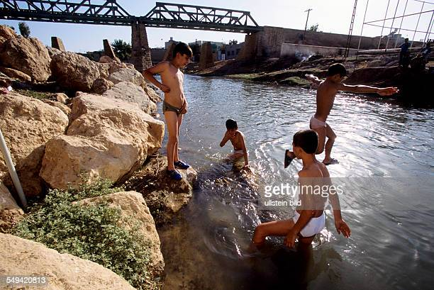 Turkey, Turkey on its way to Europe. Europe-Express, which drives from Nusaybin to Istanbul along the border to Syria. Children play under the rail...
