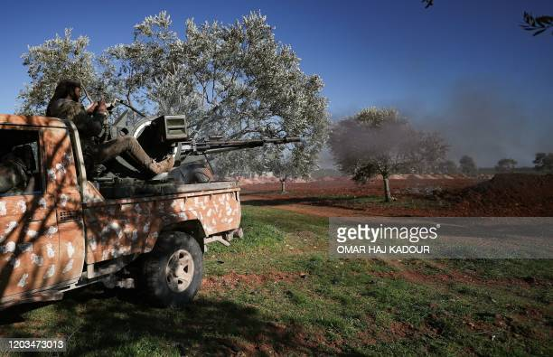 A Turkeybacked Syrian fighter fires a truckmounted gun toward the town of Saraqeb from the outskits of the villages of Afis and Salihiyah situated...