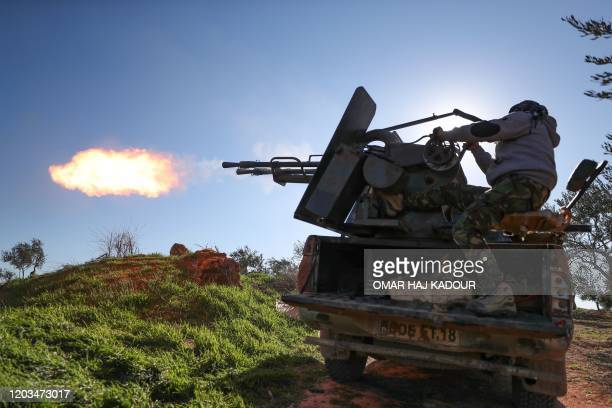 Turkey-backed Syrian fighter fires a truck-mounted gun toward the town of Saraqeb from the outskits of the villages of Afis and Salihiyah situated...