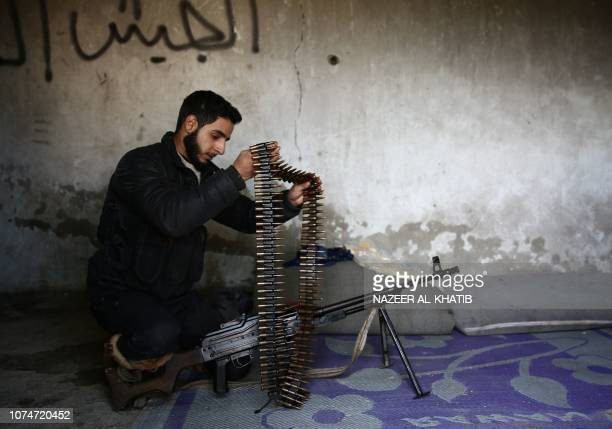 Turkeybacked Syrian fighter loads his rifle with ammunition in the town of Qirata near the rebelheld border town of Jarabulus on December 24 2018...