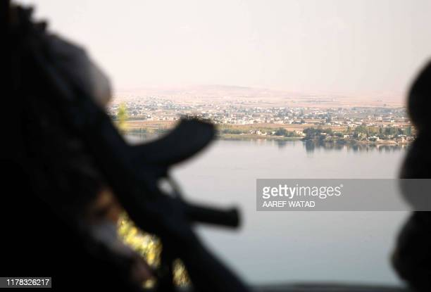 Turkey-backed Syrian fighter looks on from a fortified position near the village of Awshariyah overlooking the Euphrates river, south of Jarabulus in...