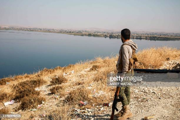 Turkey-backed Syrian fighter looks on from a position near the village of Awshariyah overlooking the Euphrates river, south of Jarabulus in the...