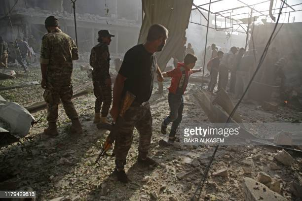 Turkey-backed Syrian fighter pulls a boy away from the site of a car bomb explosion in the northern Syrian Kurdish town of Tal Abyad, on the border...
