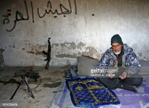 Turkeybacked Syrian fighter recites a prayer in the town of Qirata near the rebelheld border town of Jarabulus on December 24 2018 Residents and...