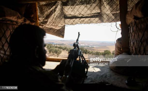 Turkey-backed Syrian fighter stands behind a machine gun at a fortified position near the village of Awshariyah overlooking the Euphrates river,...