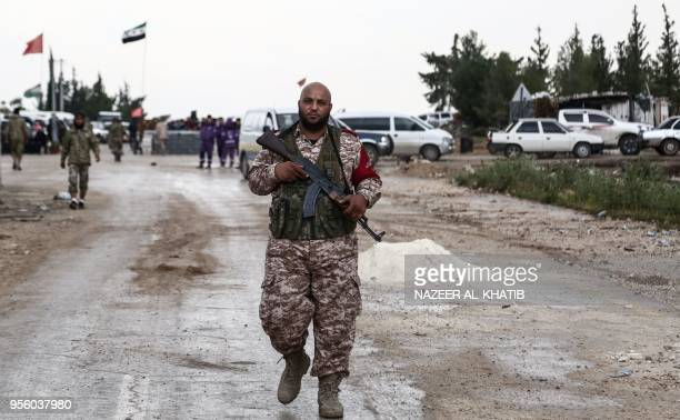 A Turkeybacked Syrian fighter walks in Abu alZandin checkpoint near alBab in northern Syria on May 8 as a convoy of buses carrying people evacuated...