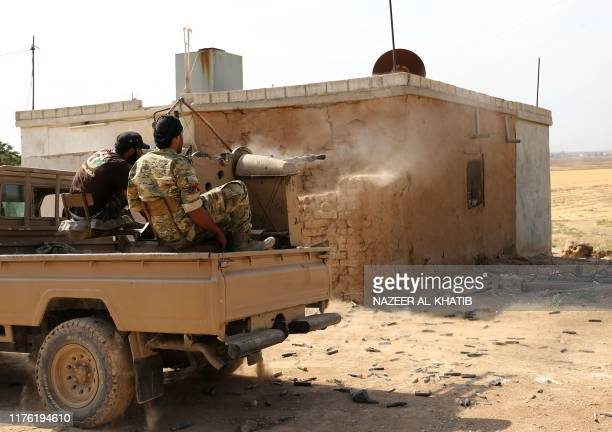 Turkeybacked Syrian fighters fire a truckmounted gun toward the key Syrian border town of Ras alAin on October 16 2019 during the ongoing assault by...