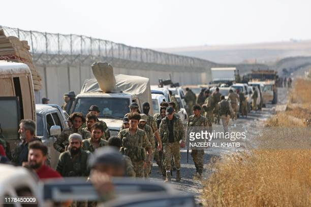 Turkeybacked Syrian fighters gather along the border between Syria and Turkey near the border town of Ras alAin in the Hassakeh province in...